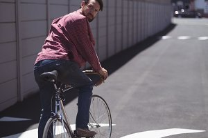 Man looking over shoulder while riding bicycle during sunny day