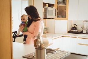 Mother feeding her little baby girl from the milk bottle in kitchen