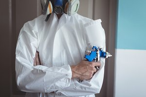 Mid section of employee holding paint spray gun at workshop