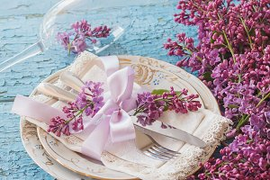 Tableware and silverware with bouquet of light violet lilac