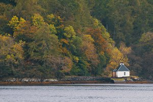 Traditional white house on scottish lake in highland