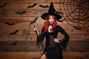 Halloween witch concept - Happy Halloween red hair Witch holding posing with magic broomstick over old wooden studio background.