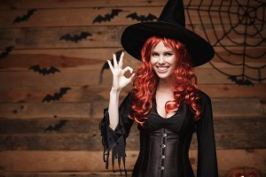 Halloween witch concept - Happy Halloween red hair Witch holding ok sign with fingers posing over old wooden studio background.