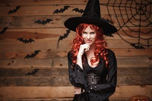 Halloween witch concept - Happy Halloween red hair Witch holding hand on her chin posing over old wooden studio background.