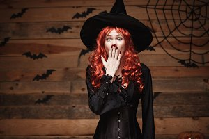 Halloween witch concept - Happy Halloween red hair Witch holding posing with shocked face over old wooden studio background.