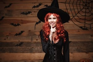 Halloween witch concept - Happy Halloween red hair Witch doing silence gesture with finger on her lips over old wooden studio background.