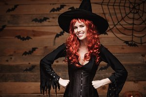 Halloween witch concept - Happy Halloween red hair Witch holding posing over old wooden studio background.