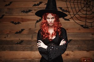 Halloween witch concept - Halloween red hair Witch holding arms posing with angry face over old wooden studio background.