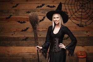 Halloween witch concept - Happy Halloween Sexy Witch holding posing over old wooden studio background.