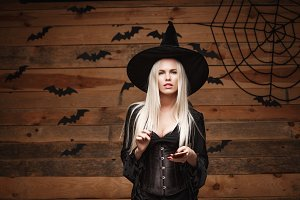 Halloween witch concept - Happy Halloween Sexy Witch holding posing with smartphone over old wooden studio background.