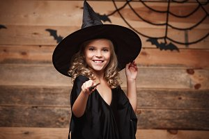 Halloween Witch concept - little witch child enjoy playing with magic wand. over bat and spider web background.