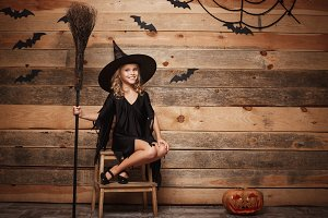 Halloween Witch concept - Full-length shot of little caucasian witch child posing with magic broomstick over bat and spider web background.