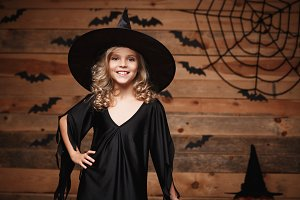 Halloween Witch concept - closeup shot of little caucasian happy witch child posing over bat and spider web background.