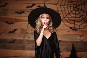 Halloween Witch concept - closeup shot of little caucasian witch child holding index finger at lips, asking to keep silence.