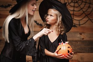 Halloween Concept - beautiful caucasian mother playing with her little daugther enjoy with Halloween candy and sweet over bats and spider web on Wooden studio background.