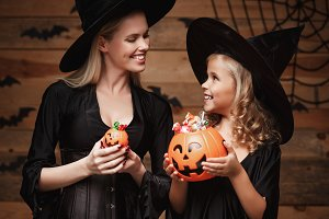 Halloween Concept - beautiful caucasian mother and her daughter in witch costumes celebrating Halloween with sharing Halloween candy and sweet over bats and spider web on Wooden studio background.