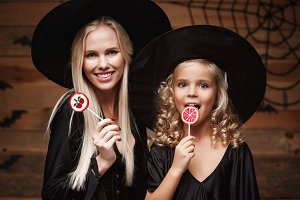 Halloween Concept - beautiful caucasian mother and her daughter in witch costumes celebrating Halloween with Halloween candy and sweet over bats and spider web on Wooden studio background.