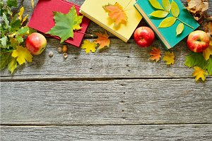 Vintage Autumn table with apples, fallen leaves, vintage books, cup of coffee or tea on old wooden table