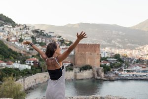 Traveller woman with arms spread looking at the bay of Alanya