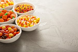 Halloween candy and sprinkles in white bowls