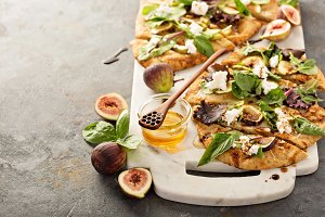 Flatbread pizza with figs, cheese and salad leaves