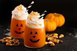Halloween cold cocktail or drink with jack o'lantern face