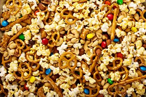 Homemade trail mix with chocolate candy, popcorn, pretzels and nuts