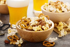 Homemade trail or snack mix with popcorn, pretzels and nuts with beer