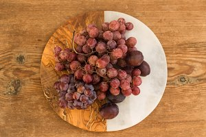 Red grapes and plums on marble and wooden background