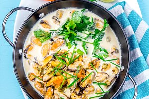 Mussels in creamy milk sauce with aromatic herbs and lemon. Top view Blue background. Top view
