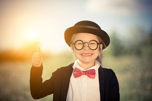 Funny little girl in bow tie and bowler hat showing thumb up.