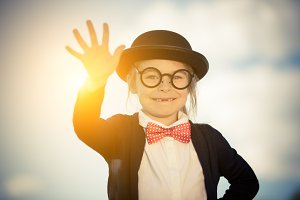 Funny little girl in bow tie and bowler hat with hello gesture.