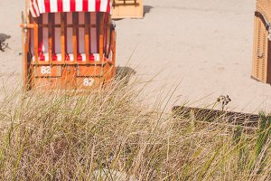 Roofed wooden chair on sandy beach in Travemunde, North Germany. Dune with grass in foreground