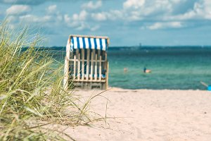 Dune with some grass and traditional wooden beach chairs on the sandy beach. Northern Germany, on the coast of Baltic Sea