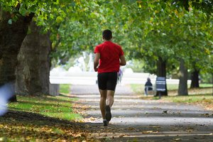 Young man in red - is running at the park