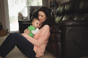 Mother embracing baby girl in living room