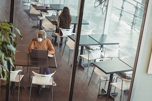 Female executive having coffee while using laptop in cafeteria