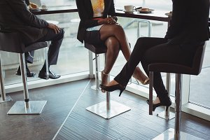 Business colleagues with legs crossed sitting on chairs