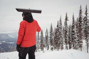 Man holding snow shovel in ski resort
