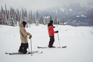 Two men skiing on snowy alps in ski resort