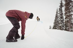 Two men working on snowy slopes in ski resort