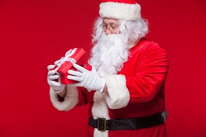 Christmas. Photo Santa Claus giving xmas present and looking at camera, on a red background