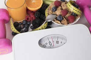scale with fruit and tape measure, concept of diet