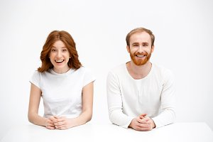 Surprised redhead girl and boy sitting at white desk with smile