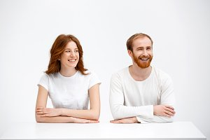 Tenderless redhead girl and boy sitting at white desk