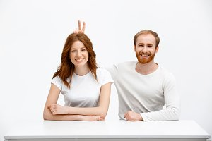 Funny redhead girl and boy sitting at white desk  play the fo