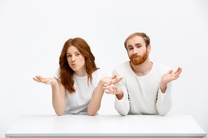 Confused redhead girl and boy sitting at white desk