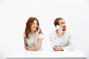Tenderless redhead girl and boy talking on phones  sitting at