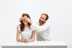 Tenderless funny redhead girl and boy sitting at white desk