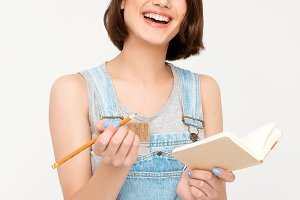 portrait of young laughing beautiful girl, holding notebook